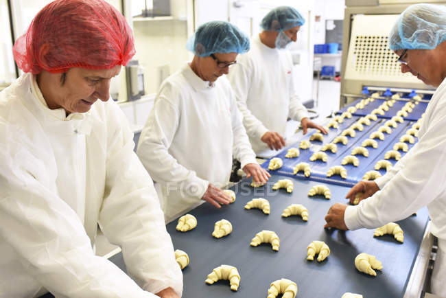 Workers at production line in a baking factory with croissants — Stock Photo