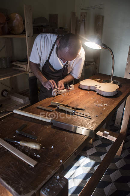 Luthier using a chisel on a violin scroll during the manufacture of a violin in his workshop — Stock Photo