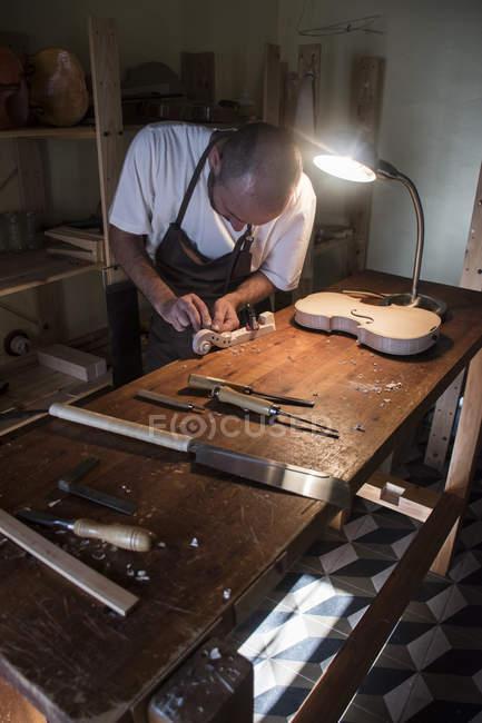 Лютье использует зубило на скрипичном свитке во время изготовления скрипки в своей мастерской — стоковое фото