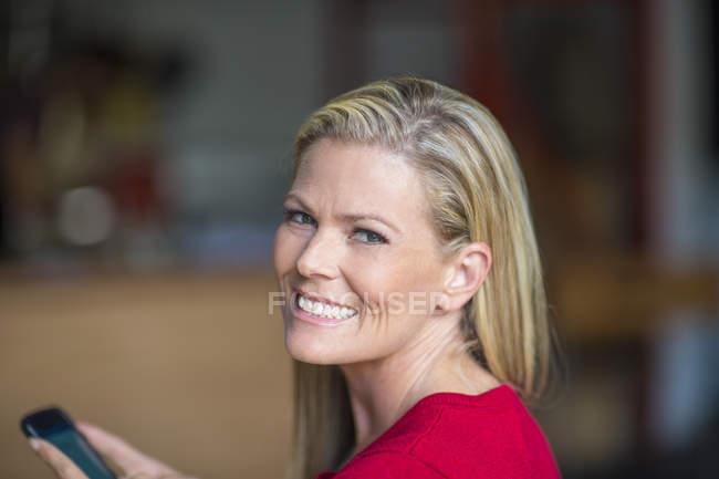 Ritratto di donna sorridente che tiene il cellulare — Foto stock