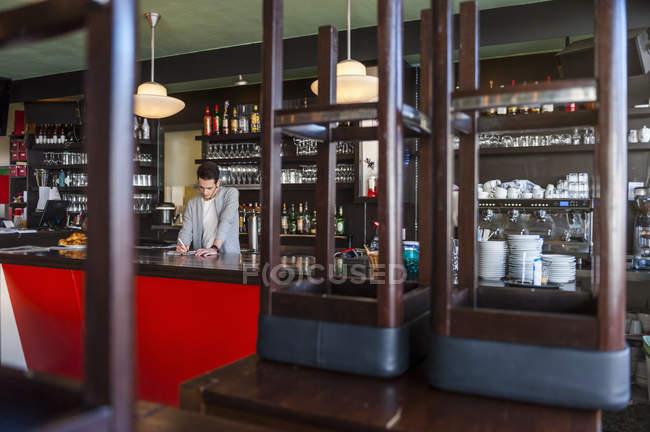 Homme derrière le comptoir d'un café, prendre des notes — Photo de stock