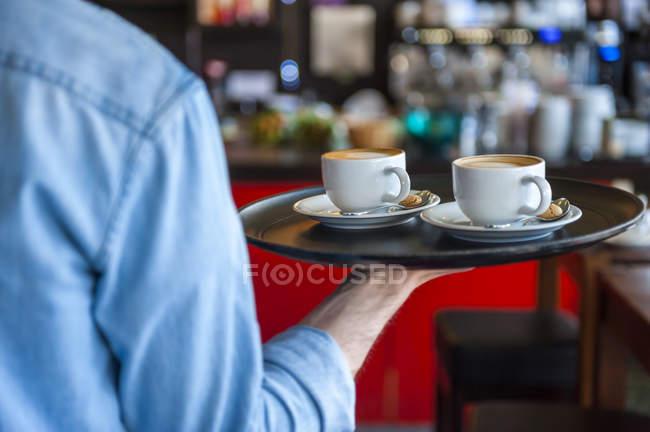 Офіціант, несучи лоток капучино чашок в кафе — стокове фото