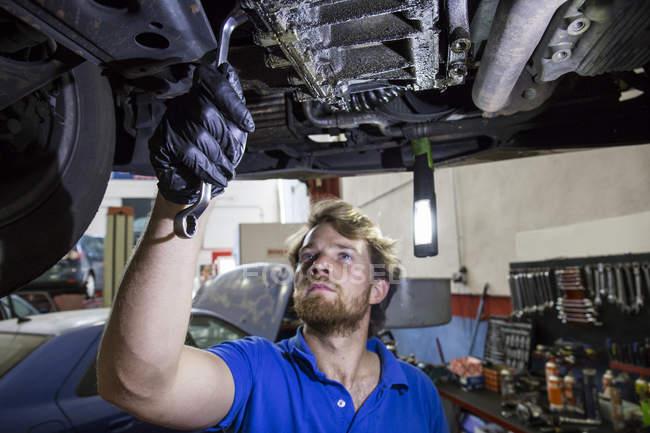 Mechaniker, die Festsetzung von angehaltenen Auto in seiner Werkstatt — Stockfoto