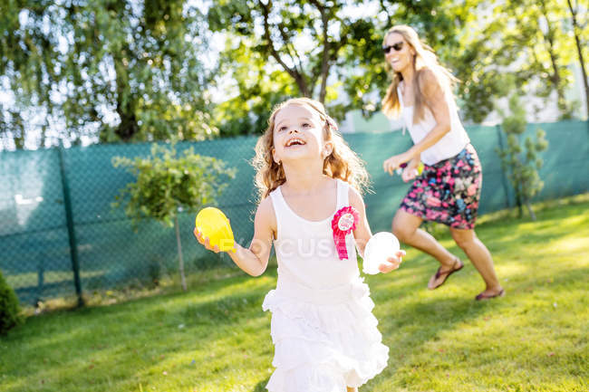 Little girl having fun with water bombs in the garden — Stock Photo