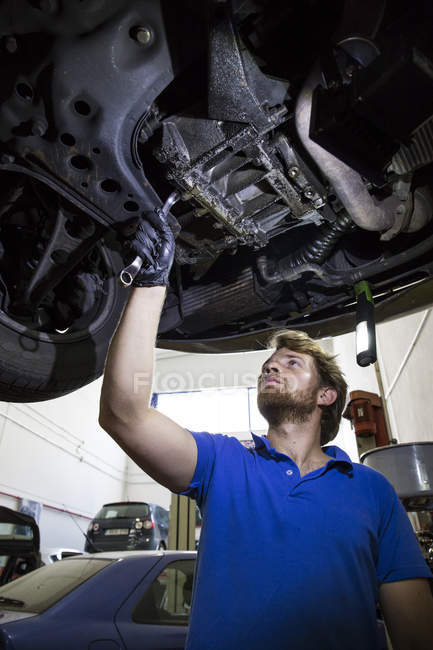 Mechanic fixing suspended car in his workshop — Stock Photo