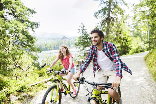 Молодая пара катается на велосипедах на природе — стоковое фото