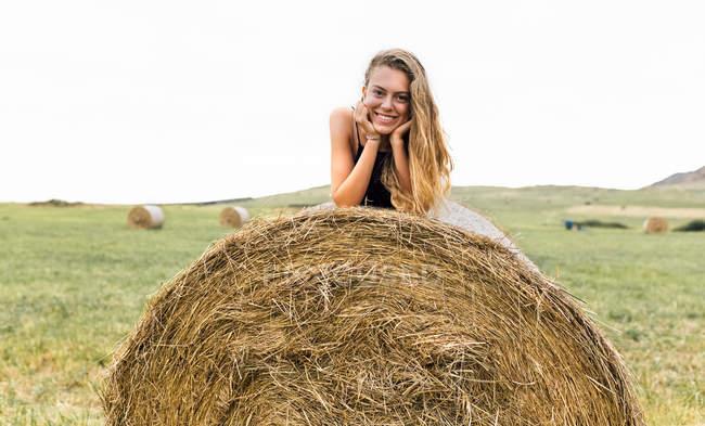 Портрет улыбающейся блондинки-подростка, лежащей на соломенном тюке — стоковое фото