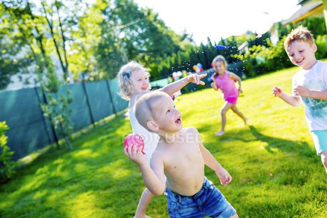 Children having fun with water bombs in the garden — Stock Photo