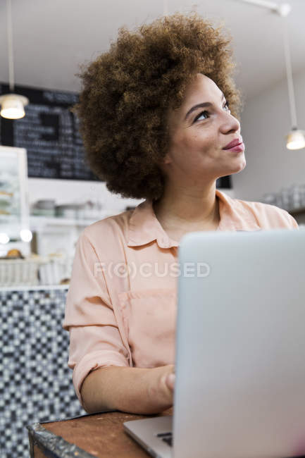 Smiling young woman with laptop in a cafe looking up — Stock Photo