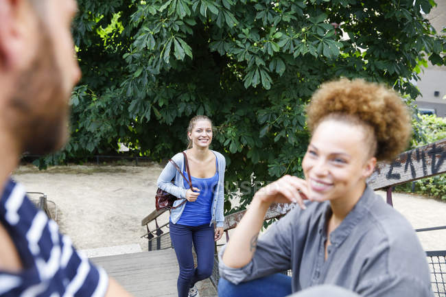Souriant jeune femme marchant dans les escaliers dans le parc avec l'homme et la femme dans foregrund — Photo de stock