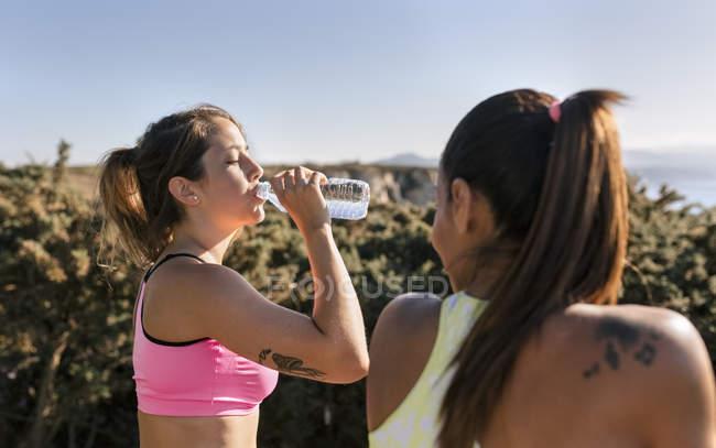 España, Asturias, dos deportistas entrenando en la costa, botella de agua, bebiendo - foto de stock