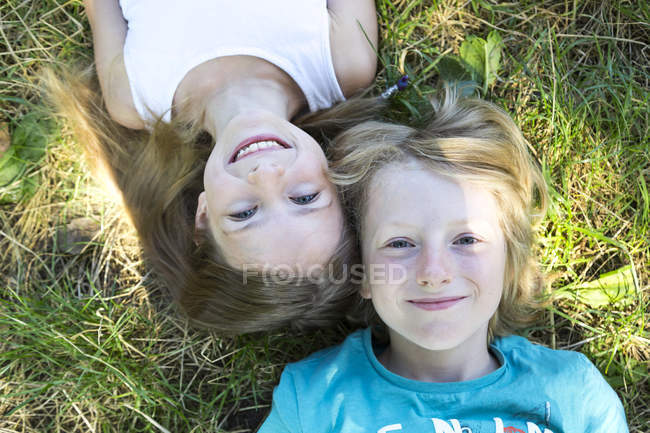 Portrait of brother and little sister lying on a meadow and looking at camera — Stock Photo