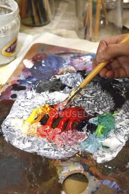 Artista con pennello e tavolozza dell'artista, vista parziale — Foto stock