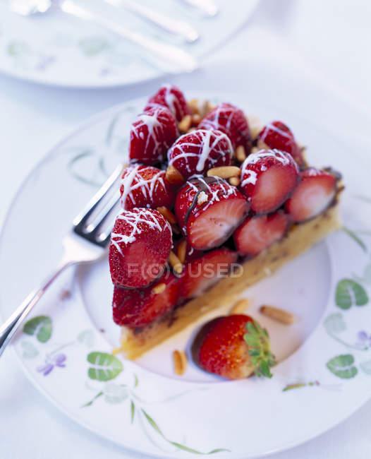 Pezzo di torta a strati fragola con pinoli e glassa al cioccolato — Foto stock