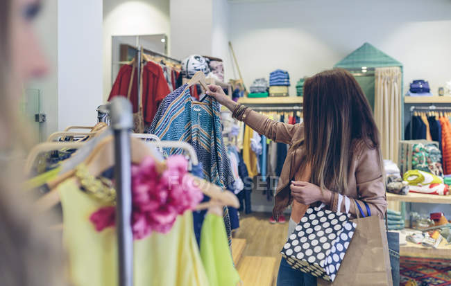 Woman shopping for clothes in a boutique — Stock Photo