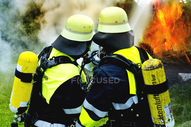 Fire brigade extinguishing fire in nature — Stock Photo