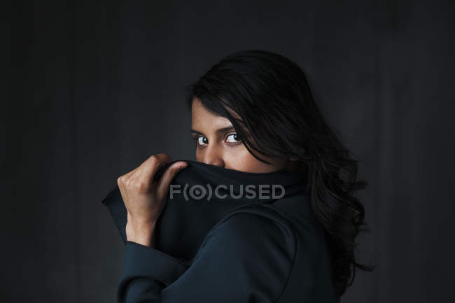 Portrait of female indian, obscured face against black background — Stock Photo