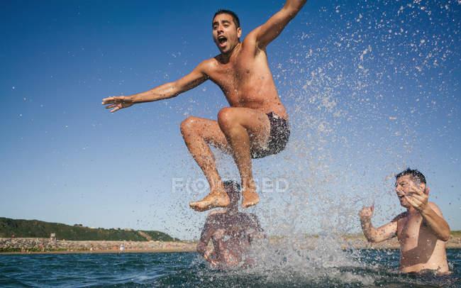 Tre amici giocosi che hanno divertimento nel mare — Foto stock