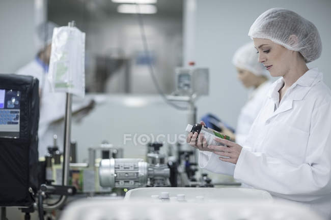 Woman in pharmaceutical plant looking at flask — Stock Photo