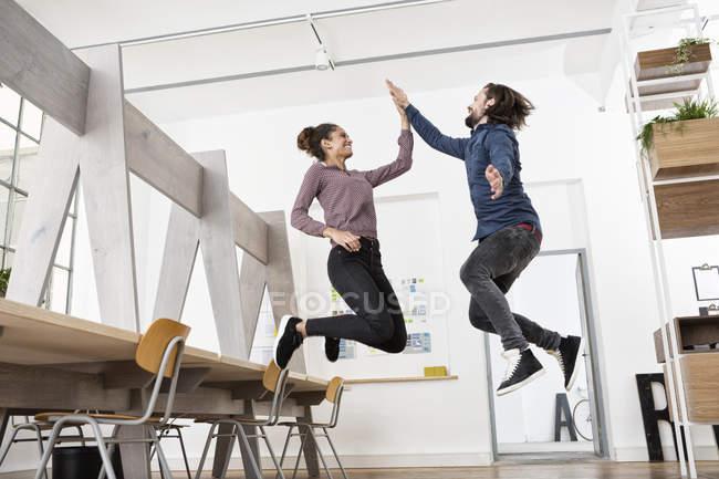 Deux collègues heureux dans le bureau sautant et haut cinq — Photo de stock