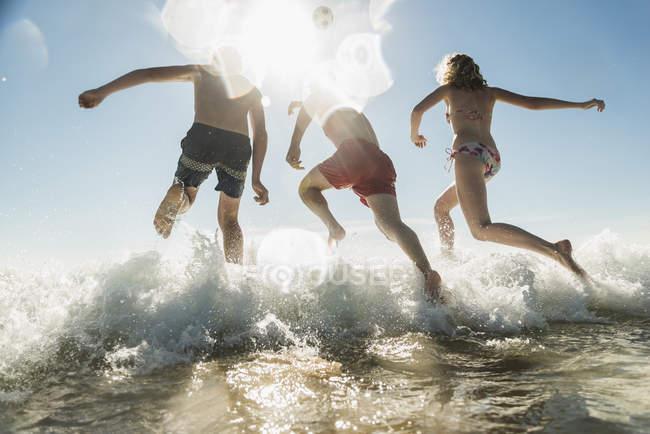 Vue arrière d'amis sautant dans la mer — Photo de stock