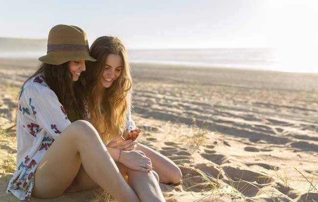 Two best friends sitting on the beach looking at smartphone — Stock Photo