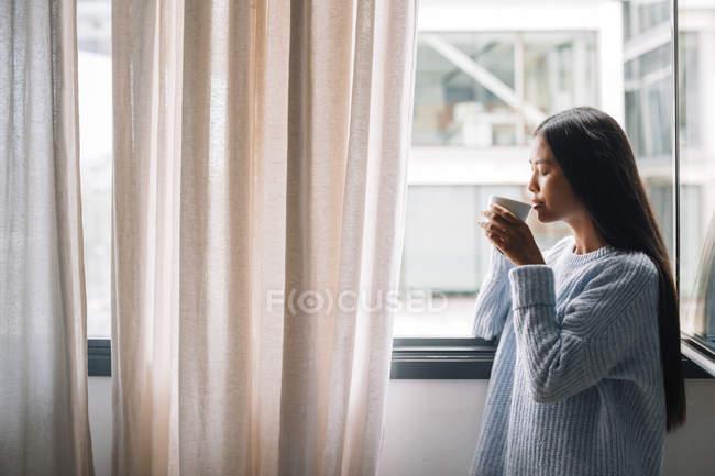 Жінка з кави стоячи перед вікном — стокове фото