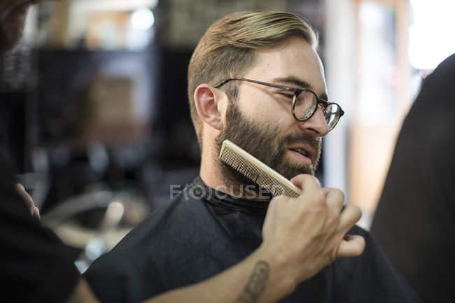 Barber combs beard of customer at barbershop — Stock Photo