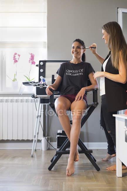 Visagiste styling smiling customer in beauty salon — Stock Photo