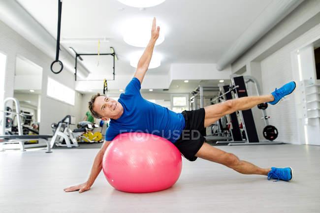 Senior man doing gymnastics on fitness ball in gym — Stock Photo