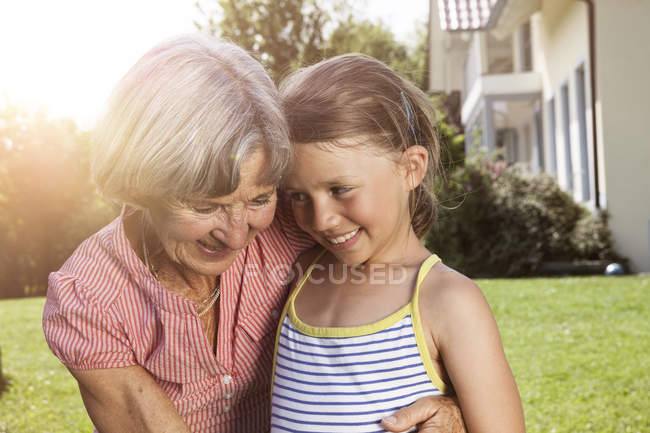 Happy grandmother and granddaughter in garden — Stock Photo