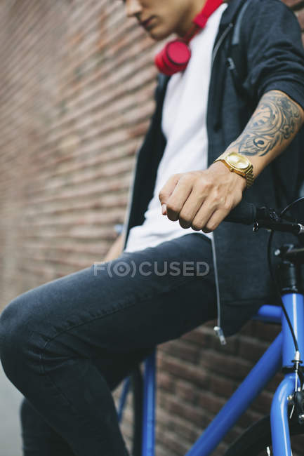 Teenager with a fixie bike, golden watch and tattoo on forearm — Stock Photo