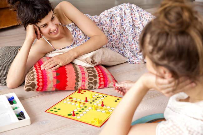 Zwei beste Freundinnen, die auf dem Boden zu Hause spielen ludo — Stockfoto