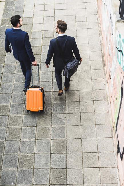 Businessmen walking with wheeled luggage — Stock Photo