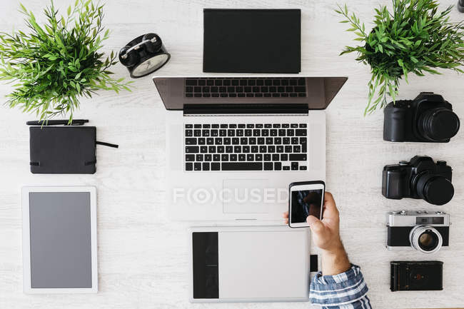 Photographer working at desk holding smartphone, partial view — Stock Photo