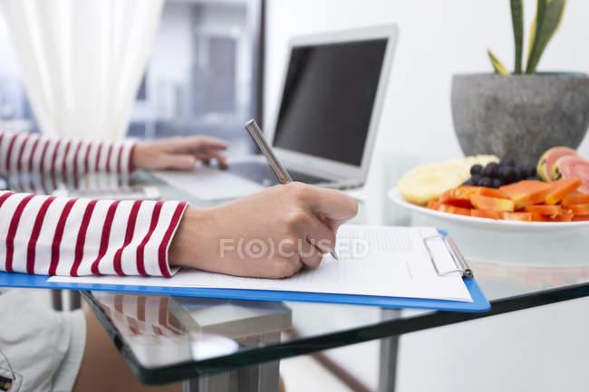 Prendre des notes sur le presse-papiers femme — Photo de stock