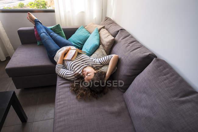 Donna rilassante sul divano di casa — Foto stock