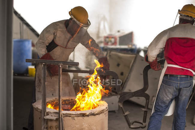 Two workers in protective workwear in smithy — Stock Photo
