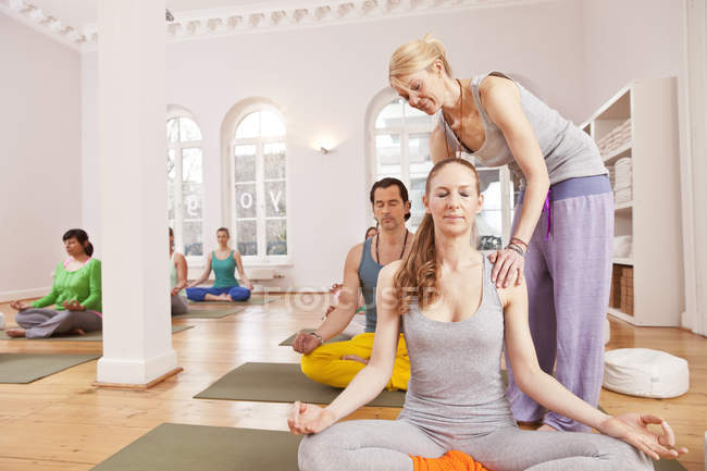 People with instructor in yoga studio sitting in Lotus pose — Stock Photo