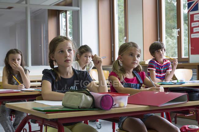 Aufmerksame Schüler am Unterricht in der Schule sitzen — Stockfoto