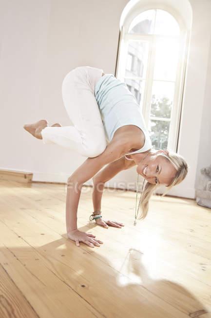 Smiling woman holding a Parsva Bakasana yoga pose — Stock Photo
