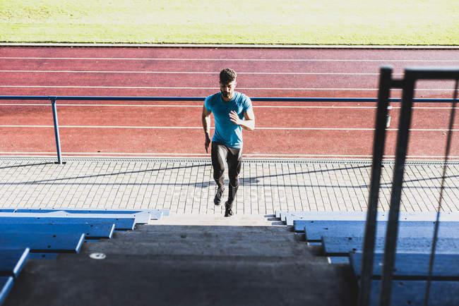Athlète s'exerçant sur la tribune d'un stade d'athlétisme — Photo de stock