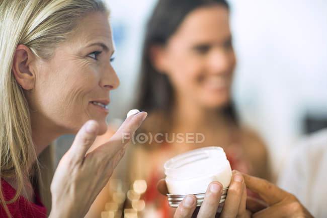Улыбающаяся женщина тестирует крем в магазине — стоковое фото