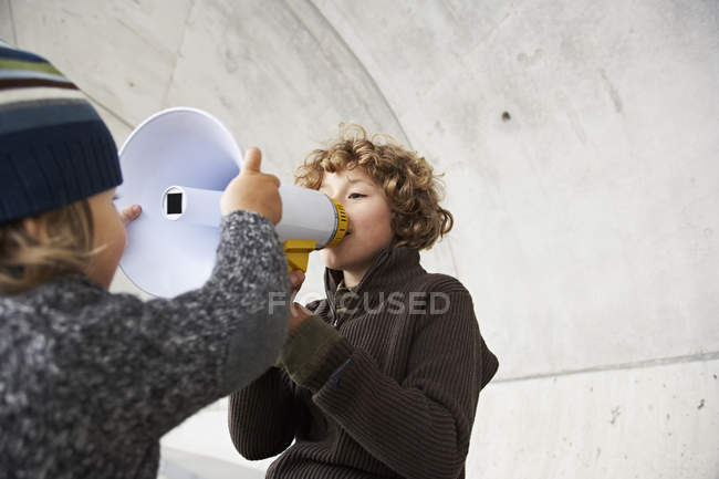 Two brothers playing with a megaphone — Stock Photo