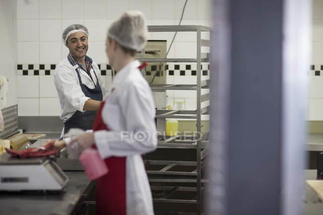 People working in butchery talking and cleaning — Stock Photo