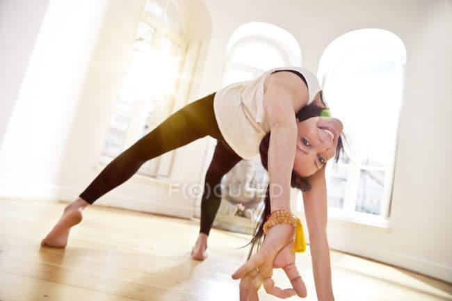 Женщина в солнечной студии йоги держит позу Урдхвы Данурасаны и улыбается в камеру — стоковое фото