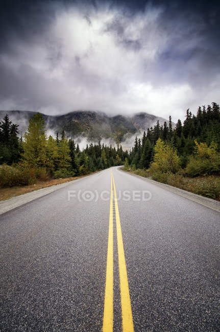 Estrada e nuvens escuras — Fotografia de Stock