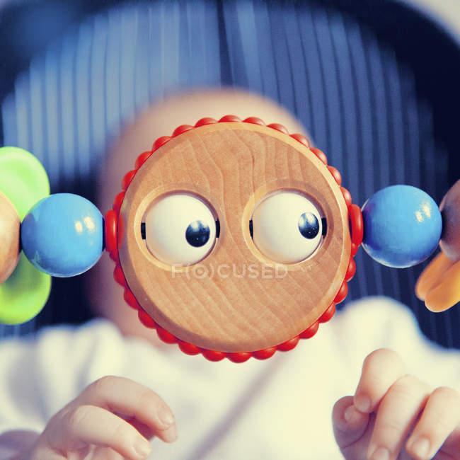 Bébé derrière un jouet aux yeux — Photo de stock