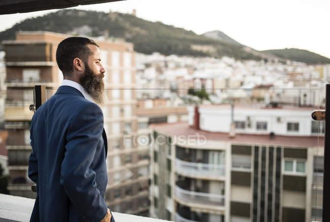 Бородатый бизнесмен, стоя на террасе на крыше — стоковое фото
