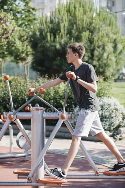 Adolescente haciendo ejercicio en el equipo de fitness al aire libre - foto de stock